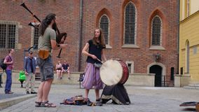 Couple of street musicians, young man and woman playing bagpipes and drum. stock video footage