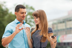 Couple on the street. Young stylishly dressed couple on the street. He shows her something on his phone Royalty Free Stock Images