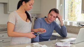 Couple stressing over finances with woman cutting credit card stock footage