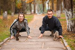 A couple stretches their leg muscles in a park in the fall lizenzfreies stockbild