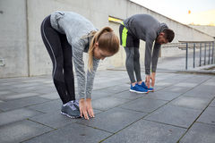 Couple stretching and bending forward on street Royalty Free Stock Photo