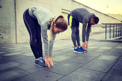 Couple stretching and bending forward on street Stock Photos