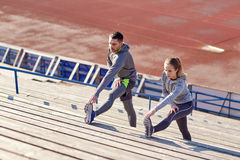 Couple stretching leg on stands of stadium Stock Images