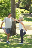 Couple stretching legs in park Stock Image