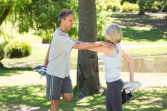 Couple stretching legs in park Royalty Free Stock Photography
