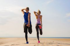 Couple stretching legs before workout stock image