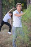 Couple stretching outdoors in forest. Couple stretching outdoors in the forest Royalty Free Stock Images