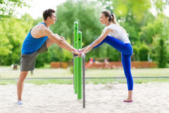 Couple stretching outdoors. Man and women exercising in the park Royalty Free Stock Photo