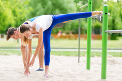 Couple stretching outdoors. Man and women exercising in the park Royalty Free Stock Image