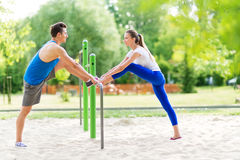 Couple stretching outdoors. Man and women exercising in the park Stock Image