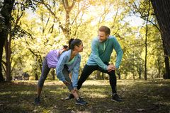 Couple stretching in park. Young couple working exercise togethe royalty free stock photography