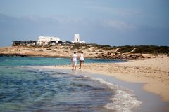 Formentera - Spain: jun 4th 2018. A couple stroll along the shore of the beach royalty free stock images