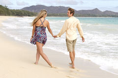 Couple stroll playfully on the beach Stock Photo