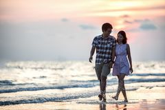 Couple strolling on beach at sunset
