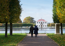 Couple Strolling in Peterhof Gardens. A man and a woman strolling with their backs to the camera in Peterhof gardens with rows of trees and grass along the dirt stock photography