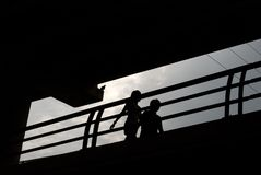 Couple Strolling in Silhouette. In silhouette, a couple strolls across a bridge as a bird watches. Travelers to Austin, Texas can use the hike and bike trails Royalty Free Stock Photo