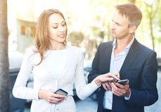 Couple strolling together, smiling and watching media in smartph Stock Photography