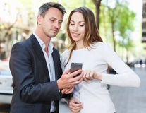 Couple strolling and using smartphone Stock Images