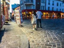 Couple strolls past tourist print shop on Montmartre, Paris, France Royalty Free Stock Images