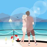 Couple stting on sailboat deck looking at sealine wearing hat with wine behind stock illustration