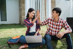 Couple student highfive while using laptop royalty free stock images