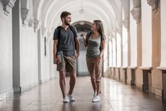 Couple of students. Attractive young students are talking and smiling while walking through the university hall Stock Images