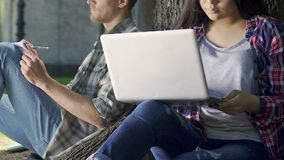 Couple of students doing their homework, girl working on laptop under tree. Stock footage stock video footage