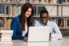Couple Of Students With Laptop In Library Royalty Free Stock Photography
