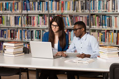 Couple Of Students With Laptop In Library. In The Library - Handsome Two College Students With Laptop And Books Working In A High School - University Library Stock Image