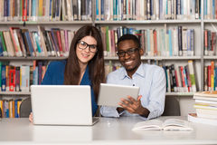 Couple Of Students With Laptop In Library. In The Library - Handsome Two College Students With Laptop And Books Working In A High School - University Library Royalty Free Stock Photos