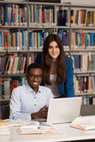 Couple Of Students With Laptop In Library. In The Library - Handsome Two College Students With Laptop And Books Working In A High School - University Library Stock Photos