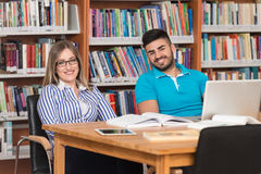 Couple Of Students With Laptop In Library Royalty Free Stock Photos