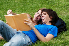 Couple students laying on the grass Royalty Free Stock Images