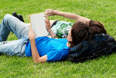 Couple students laying on the grass Stock Photography