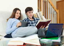 Couple students learning for examinations together. With eBook in home interior stock images