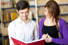 Couple of students in a library Royalty Free Stock Photos