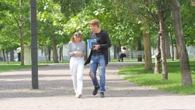 Couple of students in love walking along together. On campus, keeping book and laptop in the hands, smiling, kissing stock video