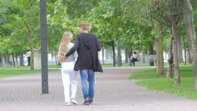Couple of students in love walking away together. On campus,in the hands of book and laptop, smiling, kissing stock footage