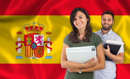 Couple of students over spanish flag Stock Images