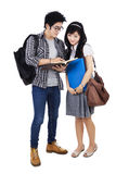 Couple students reading a book Stock Images