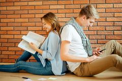 Couple students sitting outside classroom and studying together Stock Photography