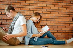 Couple students sitting outside classroom and studying together Stock Photo