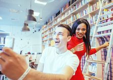Couple students in univercity library, looking book, preparing t. O exam, having fun, making selfie, lifestyle people concept close up Royalty Free Stock Image