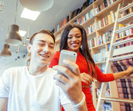 Couple students in univercity library, looking book, preparing to exam, having fun, making selfie. Lifestyle people concept Royalty Free Stock Image