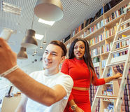 Couple students in univercity library, looking book, preparing to exam, having fun, making selfie. Lifestyle people concept Royalty Free Stock Images