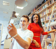 Couple students in univercity library, looking book, preparing to exam, having fun, making selfie. Lifestyle people concept Stock Image