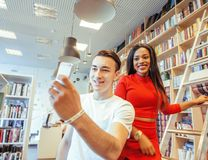 Couple students in univercity library, looking book, preparing to exam, having fun, making selfie, lifestyle people. Concept close up Royalty Free Stock Photos