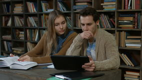 Couple of students using digital tablet in library stock footage