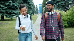 Couple of students walking outdoors on campus chatting drinking coffee. Enjoying warm autumn day and funny conversation. People and lifestyle concept stock video