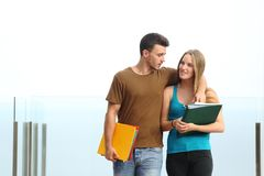 Couple of students walking towards camera. Outdoor with a white background Royalty Free Stock Image